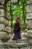 Молодая красивая девушка с длинными волосами и темным плащом смотрит вне окно старого замка от которого остались только руины в s Стоковое фото RF