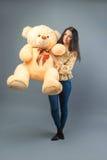 Молодая красивая девушка с усмехаться большой игрушки плюшевого медвежонка мягкой счастливый и играть на серой предпосылке стоковое фото rf