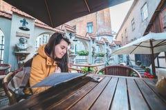 Молодая красивая еда заказа женщины в внешнем кафе в chill утре Стоковая Фотография RF