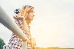 Молодая красивая женщина битника держа ретро камеру снаружи с Стоковое Фото