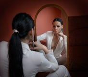 Молодая красивая женщина брюнет в элегантном белом костюме при брюки смотря в большое зеркало Обольстительный представлять девушк стоковые фотографии rf