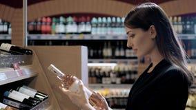 Молодая красивая женщина выбирает вино в супермаркете Брюнет в спиртном магазине сток-видео