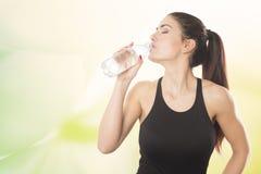 Молодая красивая женщина выпивая от бутылки воды Стоковое фото RF