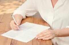 Молодая красивая женщина в белой рубашке подписывая контракт Portr Стоковое Изображение RF