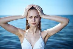 Молодая красивая женщина в белом купальном костюме купает в море, каникулах, каникулах, пляже, воде, лете Стоковое Изображение RF