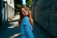 Молодая красивая женщина в голубом платье в городе в переулке, улыбка Стоковые Изображения