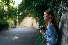 Молодая красивая женщина в голубом платье держит камеру в переулке Стоковые Изображения RF