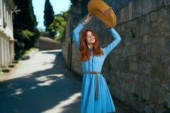 Молодая красивая женщина в голубом платье держит шляпу в переулке в городе Стоковые Фото