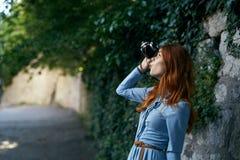 Молодая красивая женщина в голубом платье делает фото на ее камере в переулке на улице Стоковая Фотография