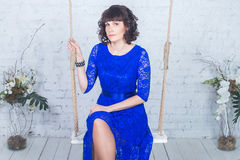 Молодая красивая женщина в голубом платье сидя на предпосылке качания белой кирпичной стены Стоковые Фотографии RF