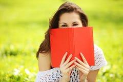 Молодая красивая женщина в парке лета с книгой Стоковое Изображение