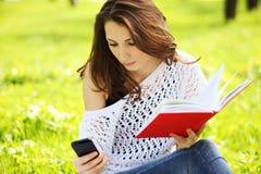 Молодая красивая женщина в парке с книгой читая messa Стоковые Фотографии RF