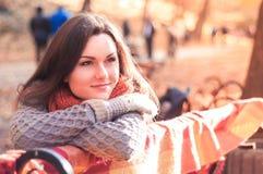 Молодая красивая женщина в связанном свитере сидя на стенде в парке осени Стоковая Фотография RF