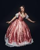 Молодая красивая женщина в средневековом платье делая реверанс на черноте Стоковое Фото