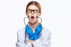 Молодая красивая женщина в стеклах и в медицинской робе держит стетоскоп на предпосылке изолированной белизной, докторе медицина, Стоковое Фото