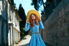 Молодая красивая женщина в шляпе и в голубом платье в переулке в городе в лете Стоковые Фотографии RF