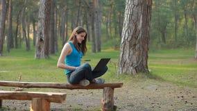 Молодая красивая женщина говоря и работая используя компьтер-книжку в природе фокусировать видеоматериал