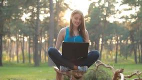 Молодая красивая женщина говоря и работая используя компьтер-книжку в заходе солнца сток-видео
