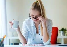 Молодая красивая женщина держа чашку кофе и читая newspa Стоковая Фотография