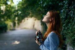 Молодая красивая женщина держит камеру на улице в переулке Стоковое Фото