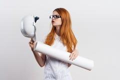 Молодая красивая женщина держит трудную шляпу и светокопии на белой предпосылке, инженере, конструкции Стоковое Фото
