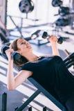 Молодая красивая женщина делая тренировки с гантелью в спортзале Стоковое Изображение RF