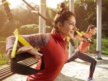 Молодая красивая женщина делая тренировку фитнеса с ремнями подвеса Стоковые Фото