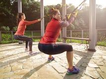 Молодая красивая женщина делая тренировку фитнеса с ремнями подвеса Стоковая Фотография RF