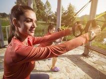 Молодая красивая женщина делая тренировку фитнеса с ремнями подвеса Стоковые Фотографии RF
