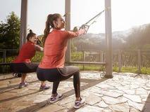 Молодая красивая женщина делая тренировку фитнеса с ремнями подвеса Стоковые Изображения RF