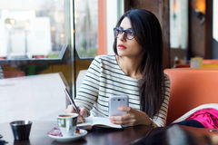Молодая красивая женщина используя ее мобильный телефон в кофе Стоковые Изображения