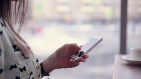 Молодая красивая женщина используя телефон сидя в стильном кафе сток-видео