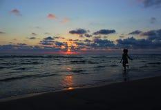 Молодая красивая женщина идя вдоль пляжа на море в вечере Стоковые Фото