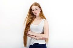 Молодая красивая женщина модели beginner redhead в голубых джинсах белой футболки практикуя представлять показывающ эмоции стоя п Стоковые Изображения RF