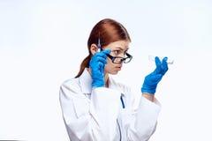 Молодая красивая женщина на белой предпосылке в медицинских мантии и стеклах держит шприц и испытания, медицину, доктора Стоковая Фотография RF