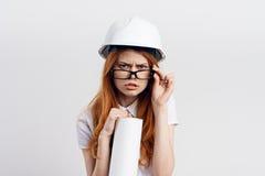 Молодая красивая женщина на белой предпосылке держит светокопии в трудной шляпе, инженерстве, конструкции Стоковое Изображение