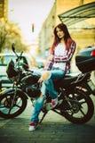 Молодая красивая женщина на мотоцикле стоковое изображение