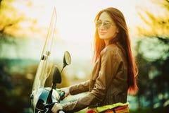 Молодая красивая женщина на мотоцикле стоковое фото