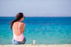Молодая красивая женщина на пляже во время тропических каникул Кофе питья девушки холодный на одном из красивых пляжей внутри Стоковое Изображение RF