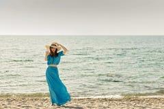 Молодая красивая женщина на пляже в лазурном длинном платье принимает pic стоковая фотография