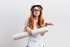 Молодая красивая женщина на светлой предпосылке держит светокопии в трудной шляпе и стеклах, конструкции Стоковое фото RF