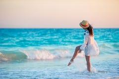 Молодая красивая женщина на тропическом пляже в заходе солнца Задний взгляд маленькой девочки в красивой предпосылке платья море стоковые фотографии rf