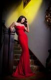 Молодая красивая женщина нося красное платье в старой гостинице Стоковое Изображение