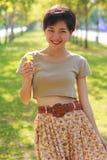 Молодая красивая женщина нося просто юбку одевает положение в парке с желтыми цветками в руке Стоковое Фото