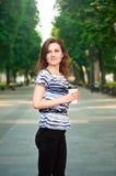 Молодая красивая женщина оставаясь в парке с кофе в ей Стоковое фото RF