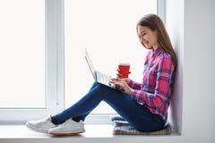 Молодая красивая женщина ослабляя на силле окна с компьтер-книжкой и cu Стоковая Фотография