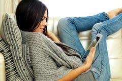 Молодая красивая женщина отдыхая на софе с планшетом стоковые изображения