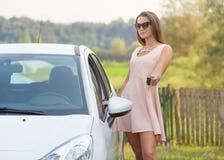 Молодая красивая женщина показывая ключ нового автомобиля стоковое изображение
