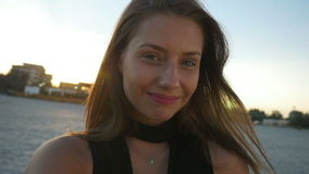 Молодая красивая женщина принимая selfie на пляже на заход солнца видеоматериал