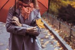 Молодая красивая женщина при зонтик представляя снаружи на времени падения Стоковые Изображения